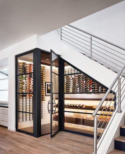 crama futuristica cu pereti din sticla sub scarile interioare